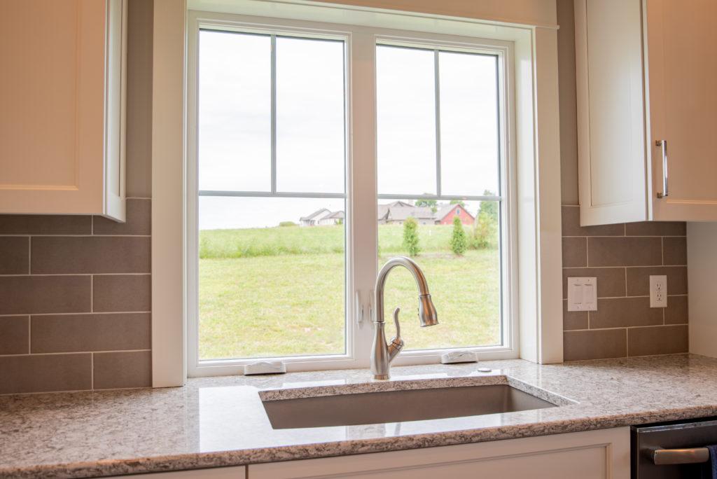 Window behind kitchen sink overlooking grassy backyard